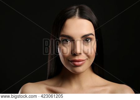 Portrait Of Happy Young Woman With Beautiful Black Hair And Charming Smile On Dark Background