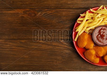 Tasty Chicken Nuggets And French Fries Served With Ketchup On Wooden Table, Top View. Space For Text