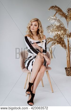 Beautiful Young Blonde Woman In An Elegant Dress And High Heel Shoes. A Woman Of Average Age 30-39 Y