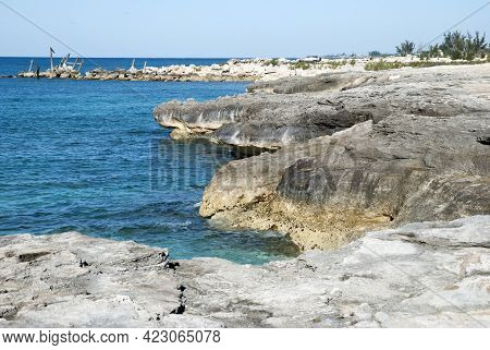 The View Of Grand Bahama Island Rocky Coastline With House Ruins In A Background.
