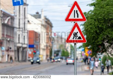 Warning Signs About Street Repairs On A Blurred Urban Background, Close-up