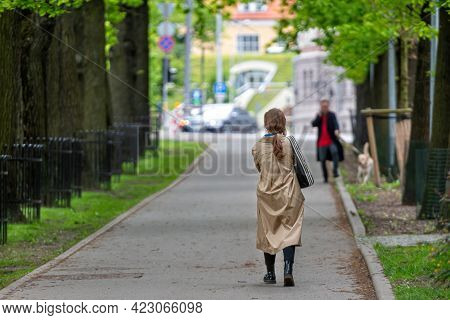 Unrecognizable People Walk Down The Sidewalk Through A Tree Alley In A City Park, Rear View