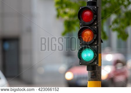 Close-up Of Small Traffic Semaphore With Green Light Against The Backdrop Of The City Traffic