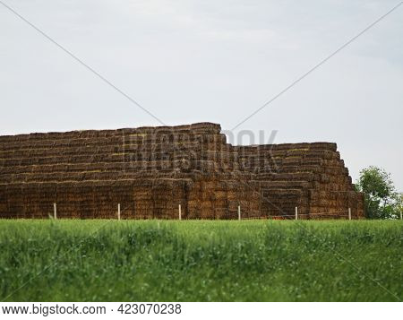 Landscape Photo Pyramid Square Stack Of Hay Bales On The Green Field.