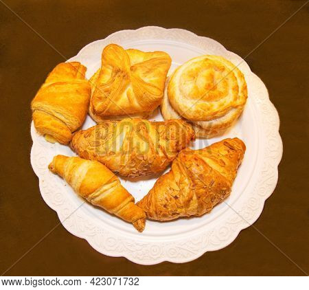 Pastry Made Of Puff Pastry In The Form Of Round Twisted Buns With Jam, Coconut Chips, Croissants On