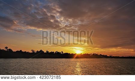 Bright Dramatic Sunset Over The River. There Are Purple Clouds In The Sky. Golden Rays Of The Sun Ov