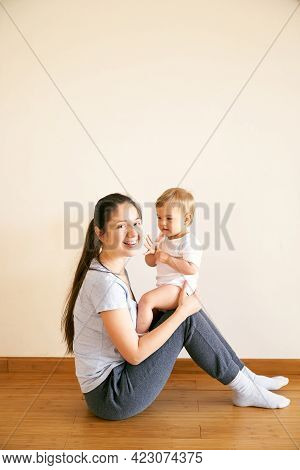 Smiling Mom Sitting On The Floor And Holding A Small Baby On Her Lap