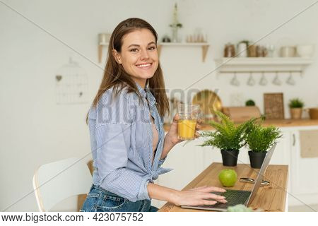 Happy Beautiful Young Woman Sitting At The Table At Home, Working In A Laptop And Drinking Delicious