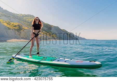 May 28, 2021. Anapa, Russia. Slim Girl On Stand Up Paddle Board At Blue Sea. Woman Vacation On Sup B