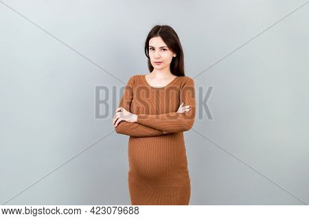 Pensive Pregnant Woman Choosing Name For Baby On Colored Background. Dream And Happy Pregnant Woman