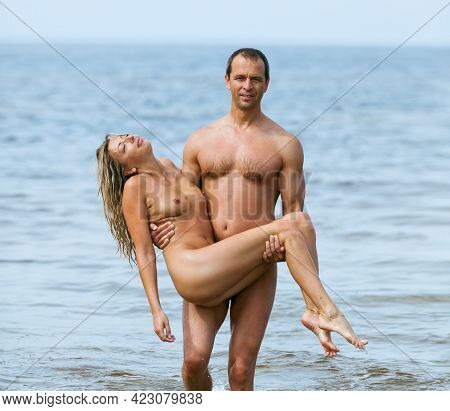Athletic Man With Naked Blonde In The Sea