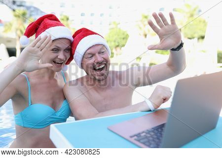 Man And Woman In Santa Claus Hats Waving Hand At Laptop Screen In Pool