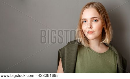 Young Smiling Attractive Woman On Dark Gray Background With Copy Space. Serious Attractive Young Wom