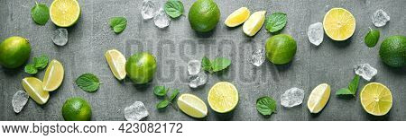 Fresh limes with ice cubes and mint leaves on wet  stone panoramic background. Applicable for kitchen glass back wall, splash back