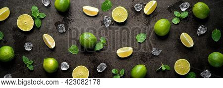 Fresh limes with ice cubes and mint leaves on dark wet panoramic background. Applicable for kitchen glass back wall, splash back