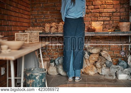 Beautiful Elegant Young Ceramicist Squeezing Piece Of Earthenware Product In Pottery Cozy Workshop