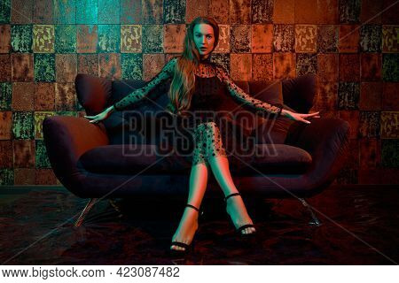 Fashion shot. Beautiful young woman in black evening dress sitting on a velvet sofa in luxury apartments. Glamorous lifestyle. Modern interior, furniture.