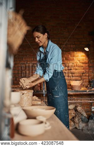 Happy Cheerful Brunette Woman Squeezing Pieces Of Earthenware Materials Above The Bucket In Pottery