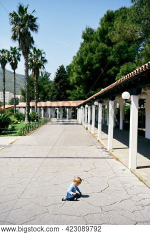 Little Girl Sits On Her Knees On The Asphalt Near A Long Pavilion In The Park