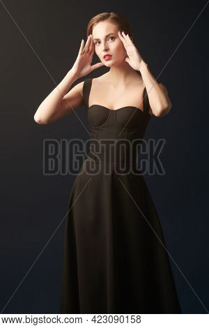 A slender beautiful girl in a black tight-fitting dress on a black background. Evening fashion. Beauty and makeup. Studio portrait.