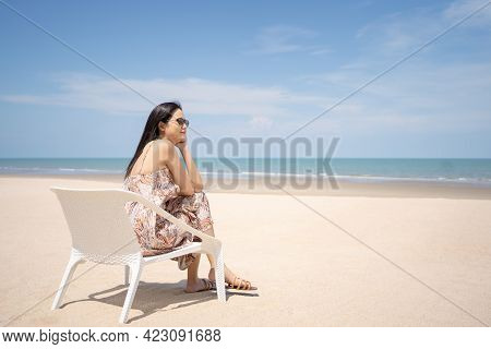 Young Women Chill Out And Sitting By The Sea Beach To Get The Sun Tan With Amazing View. Tropical Tr