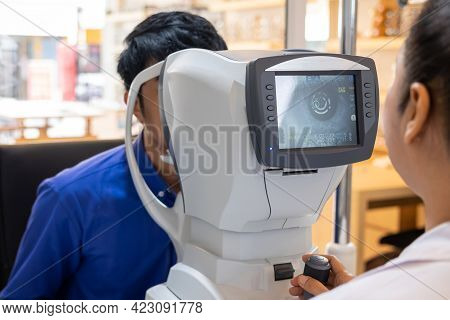 Selective Focus At Screen Of Optometry Equipment. While Optometrist Using Subjective Refraction To