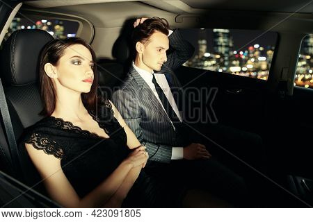 Stylish couple of young people in evening dresses driving through the city at night. Glamorous lifestyle, night party. Evening fashion.