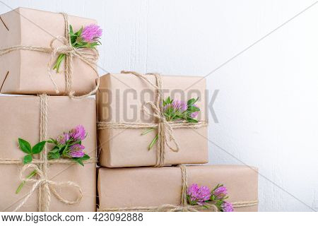 Gifts Box Wrapped With Brown Craft Paper And Decorated With Clover Flowers. Top View