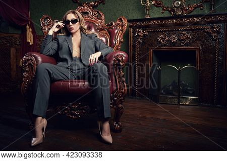 Wealthy lifestyle. Sexual woman in fashionable pantsuit and black sunglasses alluring in a vintage armchair in a luxury apartments. Fashion shot.