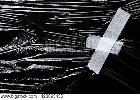 Photo Of The Polyethylene Wrap With White Tape On Black Background