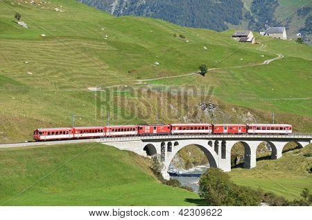 SWITZERLAND - SEP 16: Glacier Express of Matterhorn-Gotthard railway passing a bridge at Furka pass on September 16, 2012 in Switzerland.