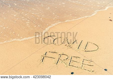 Covid Free Written On The Shore, On The Sand Of A Beach With Wave Washing The Word, Erasing Or Cance