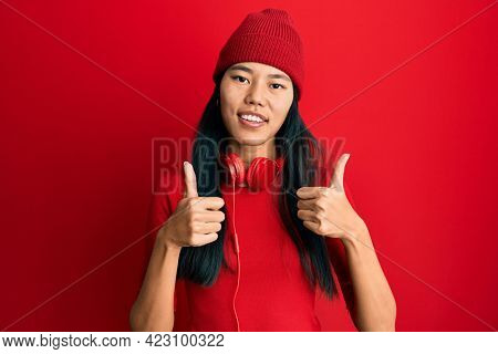 Young chinese woman listening to music using headphones success sign doing positive gesture with hand, thumbs up smiling and happy. cheerful expression and winner gesture.