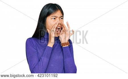 Beautiful young asian woman wearing casual clothes shouting angry out loud with hands over mouth