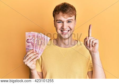 Young caucasian man holding 100 thai baht banknotes smiling with an idea or question pointing finger with happy face, number one