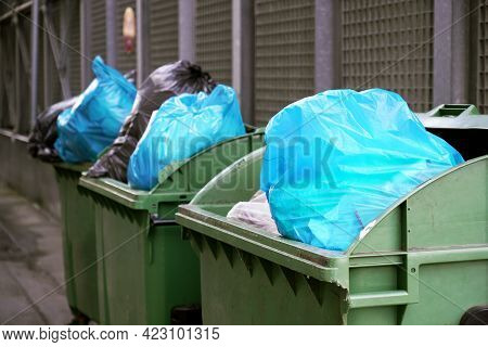 Dumpster Or Refuse Container Overflowing With Trash In Garbage Bags