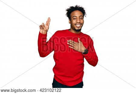 Young african american man with beard wearing casual winter sweater smiling swearing with hand on chest and fingers up, making a loyalty promise oath