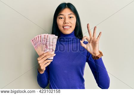 Young chinese woman holding thai baht banknotes doing ok sign with fingers, smiling friendly gesturing excellent symbol