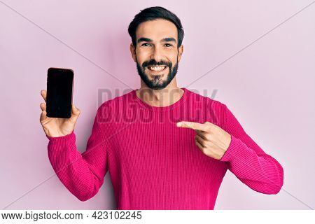 Young hispanic man holding smartphone showing blank screen smiling with a happy and cool smile on face. showing teeth.