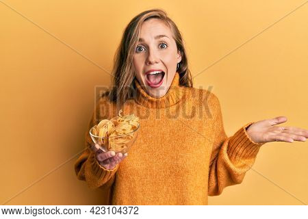 Young blonde woman holding bowl with uncooked pasta celebrating achievement with happy smile and winner expression with raised hand