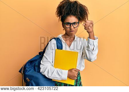Beautiful african american woman with afro hair wearing school bag and holding books annoyed and frustrated shouting with anger, yelling crazy with anger and hand raised