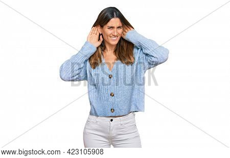 Young woman wearing casual clothes trying to hear both hands on ear gesture, curious for gossip. hearing problem, deaf