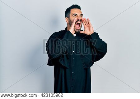 Handsome hispanic man with beard wearing catholic priest robe shouting angry out loud with hands over mouth