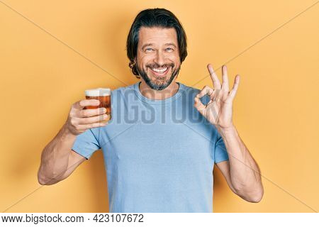 Middle age caucasian man drinking a pint of beer doing ok sign with fingers, smiling friendly gesturing excellent symbol