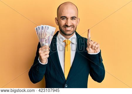 Young hispanic business man holding russian 500 ruble banknotes smiling with an idea or question pointing finger with happy face, number one
