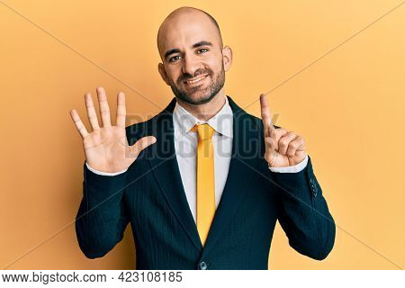 Young hispanic man wearing business suit and tie showing and pointing up with fingers number six while smiling confident and happy.