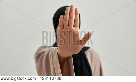 Selective Focus On Open Palm Meaning Stop Shown By Young Arabian Woman In Hijab On Light Background
