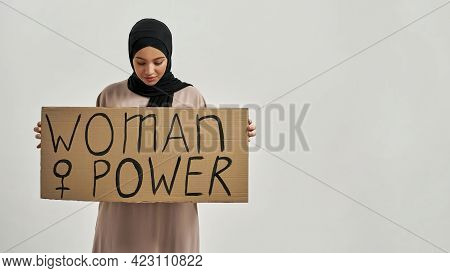 Young Arabic Woman In Traditional Hijab Holding Poster With Woman Power Quote While Posing On Light