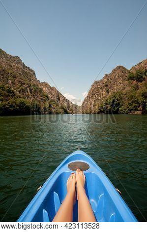 Kayaking Through River In Matka Canyon, Macedonia. Woman Legs In The Blue Kayak
