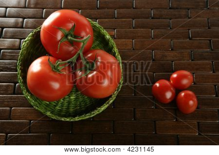 Little And Big Tomatoes In Green Basket